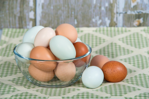 Colorful chicken eggs in glass bowl